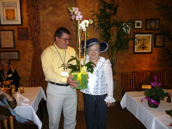 Steve presenting orchids to newly reelected President Denyse Jenkins